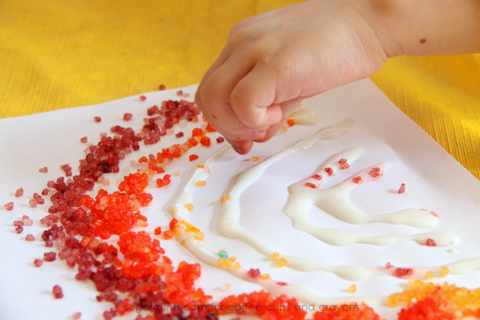 Use dyed bath salts for scented sensory art to make rainbows! This is so cute.