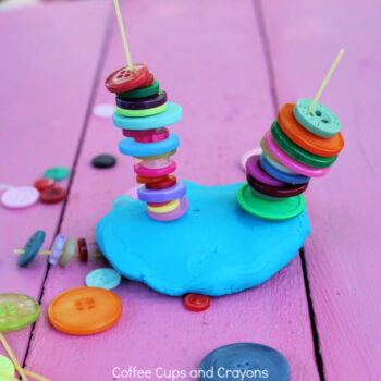 buttons stacked on dry spaghetti in the play dough
