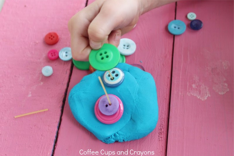 child placing buttons on the dry spaghetti in the playdough