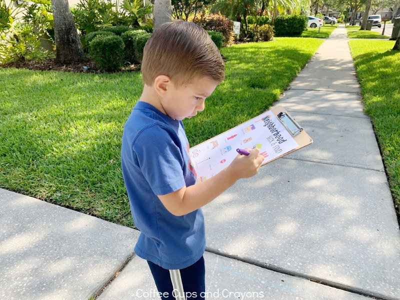 boy crossing out item on neighborhood seek and find printable
